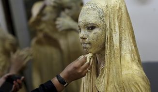 A school teacher Dresses up as a girl as a statue depicting Indian freedom leader Mahatma Gandhi's Dandi March, on the eve of Gandhi's 150th birth anniversary in New Delhi, India, Tuesday, Oct. 1, 2019. Dandi March is the name given to the Salt Satyagraha (Salt March) where Gandhi and other freedom fighters marched 241 miles to the sea to make their own salt on April 6, 1930 as an act of civil disobedience against the British colonial rule. (AP Photo/Altaf Qadri)