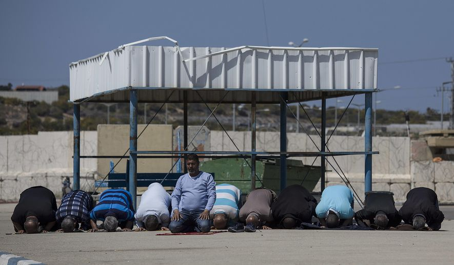 In this March 26, 2017 file photo, Palestinian residents of Gaza strip pray as they wait on the Israeli side of the Erez terminal to cross to Gaza Strip. (AP Photo/Tsafrir Abayov, File)