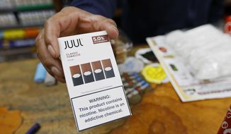 FILE - In this June 17, 2019, file photo, a cashier displays a packet of tobacco-flavored Juul pods at a store in San Francisco. Juul Labs said Monday, Sept. 30, 2019, that it will stop supporting a ballot measure to overturn an anti-vaping law in San Francisco, effectively killing the campaign. (AP Photo/Samantha Maldonado, File)