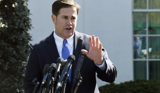 FILE - In this April 3, 2019, file photo, Arizona Gov. Doug Ducey talks to reporters outside the West Wing of the White House in Washington. A judge has ruled Monday, Sept. 30, 2019, Ducey acted illegally when he pushed a 2016 ballot measure to increase the level of K-12 education funding that could be withdrawn from Arizona's land trust without first getting approval from Congress. (AP Photo/Susan Walsh, File)