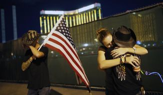 FILE - In this Oct. 1, 2018, file photo, Megan Murphy, right in hat, embraces Cara Knoedler as Kenneth Wright wipes his eyes on the first anniversary of the mass shooting in Las Vegas. In the two years since the deadliest mass shooting in modern U.S. history, the federal government and states have taken some action to tighten gun regulations. But advocates say they're frustrated more hasn't been done since the attack in Las Vegas killed 58 people on Oct. 1, 2017, and that mass shootings keep happening across the country. (AP Photo/John Locher, File)