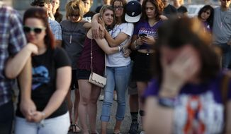 FILE - In this April 1, 2018, file photo, people comfort each other during a vigil for victims and survivors of a mass shooting in Las Vegas. In the two years since the deadliest mass shooting in modern U.S. history, the federal government and states have taken some action to tighten gun regulations. But advocates say they're frustrated more hasn't been done since the attack in Las Vegas killed 58 people on Oct. 1, 2017, and that mass shootings keep happening across the country. (AP Photo/John Locher, File)