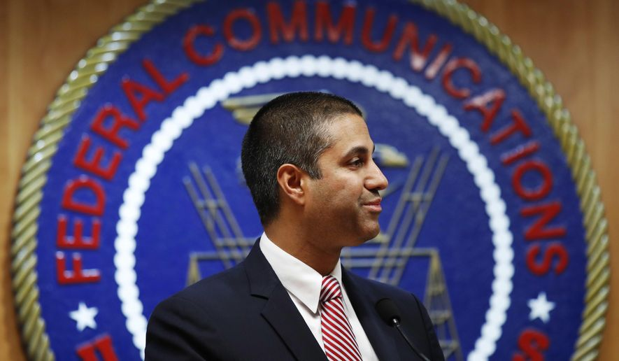 In this Dec. 14, 2017, file photo, after a meeting voting to end net neutrality, Federal Communications Commission (FCC) Chairman Ajit Pai smiles while listening to a question from a reporter in Washington. A federal court is ruling that the FCC had the right to dump net-neutrality rules, but couldn't bar states like California from passing their own. The ruling is largely a victory for Pai. (AP Photo/Jacquelyn Martin, File)