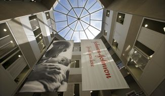 FILE - In this July 30, 2013, file photo, large banners hang in an atrium at the headquarters of Johnson & Johnson in New Brunswick, N.J. Johnson & Johnson has become the latest company to settle a lawsuit to get out of the first federal trial over the nation's opioids crisis, reaching a deal worth more than $20 million with two Ohio counties, the company announced Tuesday, Oct. 1, 2019. (AP Photo/Mel Evans, File)