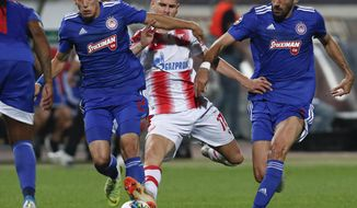 Red Star's Marko Gobeljic, center, challenges for the ball with Olympiakos' Kostas Tsimikas, left, and Andreas Bouchalakis during the Champions League group B soccer match between Red Star and Olympiacos, in Belgrade, Serbia, Tuesday, Oct.1, 2019. (AP Photo/Darko Vojinovic)