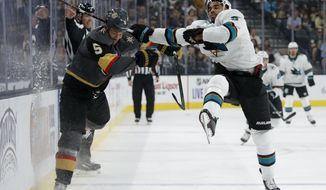 Vegas Golden Knights defenseman Deryk Engelland, left, checks San Jose Sharks left wing Evander Kane during the first period of an NHL preseason hockey game Sunday, Sept. 29, 2019, in Las Vegas. (AP Photo/John Locher)