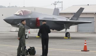 A South Korean fighter pilot, left, stands near F-35 A Stealth in the 71st anniversary of Armed Forces Day at the Air Force Base in Daegu, South Korea Tuesday, Oct. 1, 2019. (Jeon Heon-kyun/Pool Photo via AP)