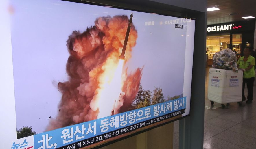 """A TV screen shows a file image of a North Korea's missile launch during a news program at the Seoul Railway Station in Seoul, South Korea, Wednesday, Oct. 2, 2019. North Korea on Wednesday fired projectiles toward its eastern sea, South Korea's military said, in an apparent display of its expanding military capabilities ahead of planned nuclear negotiations with the United States this weekend. The sign reads: """" A projectile laugh from North Korea."""" (AP Photo/Ahn Young-joon)"""