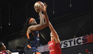 Connecticut Sun forward Jonquel Jones, left, goes to the basket against Washington Mystics forward Elena Delle Donne, right, in the first half of Game 2 of basketball's WNBA Finals, Tuesday, Oct. 1, 2019, in Washington. (AP Photo/Nick Wass)