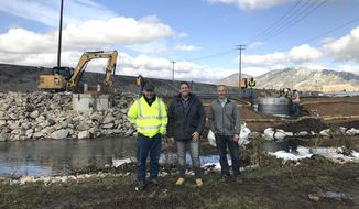 From left; Tim Hilmo, Ron Halsey and Greg Frisch of Atlantic Richfield Co., stand where treated water originating in the Berkeley Pit is being discharged into Silver Bow Creek in Butte, MT., Monday, Sept. 30, 2019. The treated water enters the creek through a pipe that's buried behind the rock wall. (Nora Saks/Montana Public Radio)