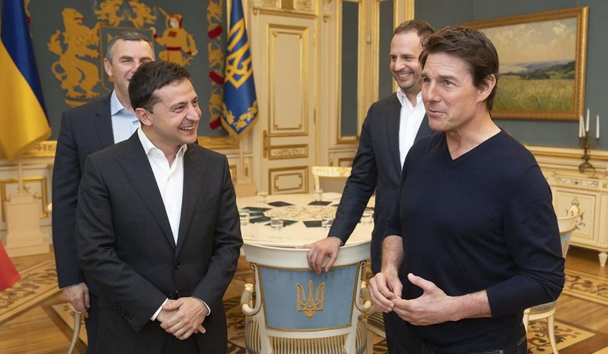 Ukrainian President Volodymyr Zelenskiy and American actor, film director and producer Tom Cruise talk to each other during their meeting in Kyiv, Ukraine, late Monday, Sept. 30, 2019. At the invitation of President of Zelensky, Tom Cruise arrived in Kyiv. (Ukrainian Presidential Press Office via AP)