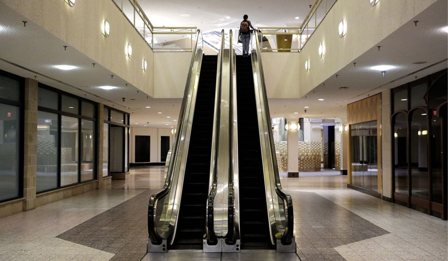 A woman rides an escalator past closed storefronts inside the largely empty White Flint Mall, Monday, Dec. 1, 2014, in Bethesda, Md. Opened in 1977, just two tenants remain as the mall's owner plans to eventually replace it with a mix of housing, office space and outdoor shopping. (AP Photo/Patrick Semansky)