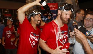 Washington Nationals catcher Kurt Suzuki, left, pours champagne on teammate Stephen Strasburg as they celebrate after winning a National League wild-card baseball game against the Milwaukee Brewers, Tuesday, Oct. 1, 2019, in Washington. Washington won 4-3. (AP Photo/Patrick Semansky)