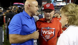 Washington Nationals General Manager Mike Rizzo, left, and Washington Nationals principal owner Mark Lerner, right, speak to each other on the field after the Washington Nationals defeat the Milwaukee Brewers 4-3 in a National League wild-card baseball game at Nationals Park, Tuesday, Oct. 1, 2019, in Washington. (AP Photo/Andrew Harnik)