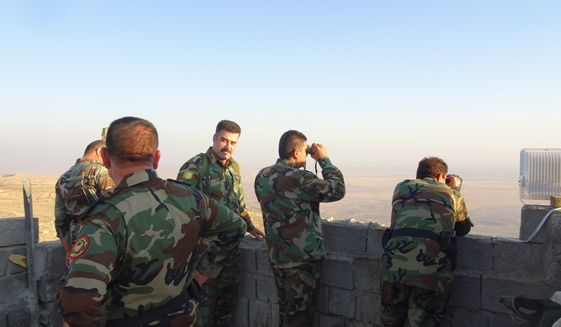 Kurdish peshmerga use binoculars to look for ISIS activity below Mount Qarachogh. (Seth J. Frantzman - Special to The Washington Times)