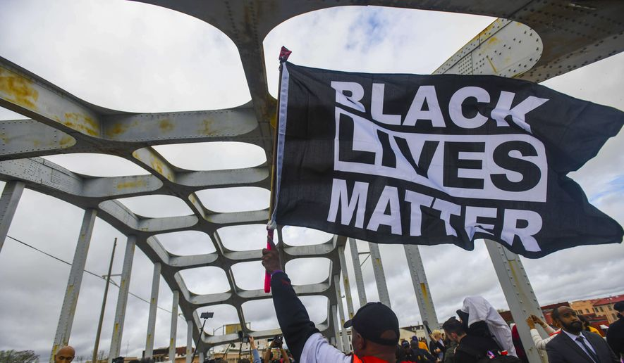 In this March 3, 2019, file photo, Black Lives Matter demonstrator waves a flag on the Edmund Pettus Bridge during the Bloody Sunday commemoration in Selma, Ala. On Nov. 13, the AP reported that a local school board in Burlington, Vt., gave its permission to an area middle school to fly the banner on campus. (AP Photo/Julie Bennett, File)