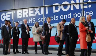 People queue to enter Manchester Central Convention Centre, where Britain's Prime Minister Boris Johnson will later deliver the Leaders's speech at the Conservative Party Conference in Manchester, England, Wednesday, Oct. 2, 2019. Britain's ruling Conservative Party is holding their annual party conference. (AP Photo/Frank Augstein)