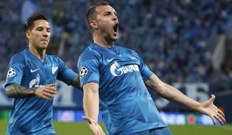 Zenit's Artem Dzyuba, right, celebrates after scoring the opening goal during the Champions League group G soccer match between Zenit St.Petersburg and Benfica at the Saint Petersburg stadium in St. Petersburg, Russia, Wednesday, Oct. 2, 2019. (AP Photo/Mike Kireev)