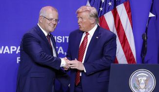 FILE - In this Sept. 22, 2019, file photo, U.S. President Donald Trump, right, and Australian Prime Minister Scott Morrison shake hands after speaking during a joint visit to mark the opening of an Australian-owned Pratt Industries plant in Wapakoneta, Ohio. Morrison on Wednesday said his country is unlikely to provide the United States with internal government communications with an Australian diplomat who is partially responsible for triggering the FBI investigation into Russian interference in the 2016 presidential election. (AP Photo/John Minchillo, File)