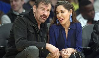 FILE - In this March 6, 2019, file photo, Henry Nicholas III, left, and Ashley Fargo watch during an NBA basketball game between the Los Angeles Lakers and the Denver Nuggets in Los Angeles.  The California technology billionaire and his friend have paid $1 million to avoid prison time while acknowledging evidence against them without admitting guilt in a Las Vegas Strip hotel room drug case. Henry Nicholas and co-defendant Ashley Fargo entered Alford pleas Wednesday, Oct. 2, 2019, in Nevada state court to two felony drug possession charges.(AP Photo/Mark J. Terrill, File)