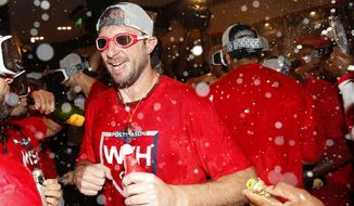 Washington Nationals starting pitcher Max Scherzer celebrates with teammates after winning a National League wild-card baseball game against the Milwaukee Brewers, Tuesday, Oct. 1, 2019, in Washington. Washington won 4-3. (AP Photo/Patrick Semansky)