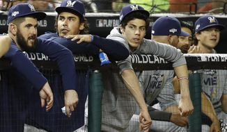 Milwaukee Brewers' Christian Yelich, third from left, sits in the dugout in the fifth inning of a National League wild card baseball game against the Washington Nationals, Tuesday, Oct. 1, 2019, in Washington. (AP Photo/Patrick Semansky)