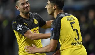 Borussia Dortmund's Achraf Hakimi, right, celebrates his goal with a teammate Raphael Guerreiro during the Champions League group F soccer match between Slavia Prague and Borussia Dortmund in Prague, Czech Republic, Wednesday, Oct. 2, 2019. (Ondrej Deml/CTK via AP)