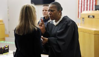 State District Judge Tammy Kemp gives advice and encouragement to former Dallas Police Officer Amber Guyger, left, before Guyger left for jail, Wednesday, Oct. 2, 2019, in Dallas. Guyger, who said she mistook neighbor Botham Jean's apartment for her own and fatally shot him in his living room, was sentenced to a decade in prison. (Tom Fox/The Dallas Morning News via AP, Pool)