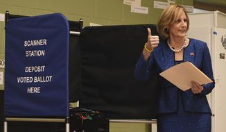 FILE -- In this Nov. 6, 2018 file photo, Republican Congresswoman Claudia Tenney signals a successful casting of her ballot in New Hartford, N.Y. Tenney has announced that she's campaigning to reclaim the seat in Congress she narrowly lost in 2018 to Democrat Anthony Brindisi. (AP Photo/Heather Ainsworth, File)