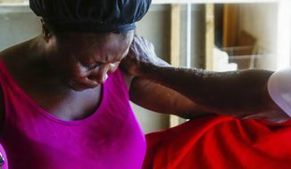 In this Sept. 16, 2019 photo, Remelda Thomas bows her head in prayer in her home in McLean's Town Cay, Grand Bahamas Island, Bahamas. Thomas said she lost eight family members in the storm. While sleeping one night after the storm the wind was blowing and the tarp over the hole in her roof was snapping and it brought back the fear from Hurricane Dorian. (Chris Day/University of Florida via AP)