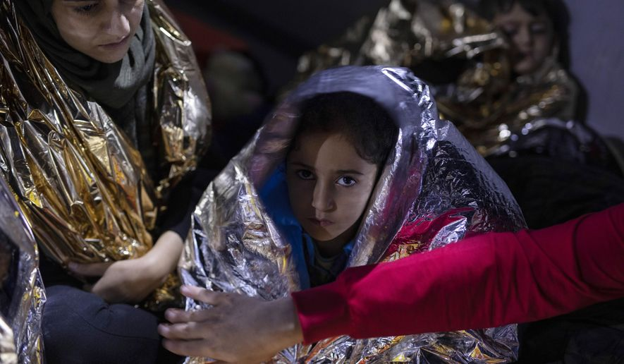 A Iraqi girl looks on as she is covered with a thermal blanket after she and other migrants and refugees were rescued by the Greek coast guard, early Thursday, Sept. 26, 2019, near the Greek island from Samos. 23 migrants and refugees from Syria, Iraq, Palestine and Iran who tried to cross the Aegean Sea from Turkey to the Greek island of Samos on a plastic boat, were rescued by the Greek coast Guard. (AP Photo/Petros Giannakouris)