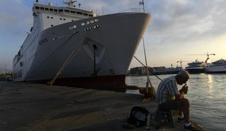 A man lights a cigarette in front of a docked ferry during a 24-hour strike at the port of Piraeus, near Athens, Wednesday, Oct. 2, 2019. Greek island ferries are tied up in port for a day while Athens public transport, hospitals and state schools face disruptions as unions strike against proposed labor reforms. (AP Photo/Michael Varaklas)