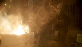 Protester react to tear gas as a fire burns on the streets of Hong Kong on Wednesday, Oct. 2, 2019. Protests continue a day after police shot a teenage demonstrator at close range during widespread anti-government demonstrations on China's National Day and marked a fearsome escalation in Hong Kong's protest violence. (AP Photo/Kin Cheung)