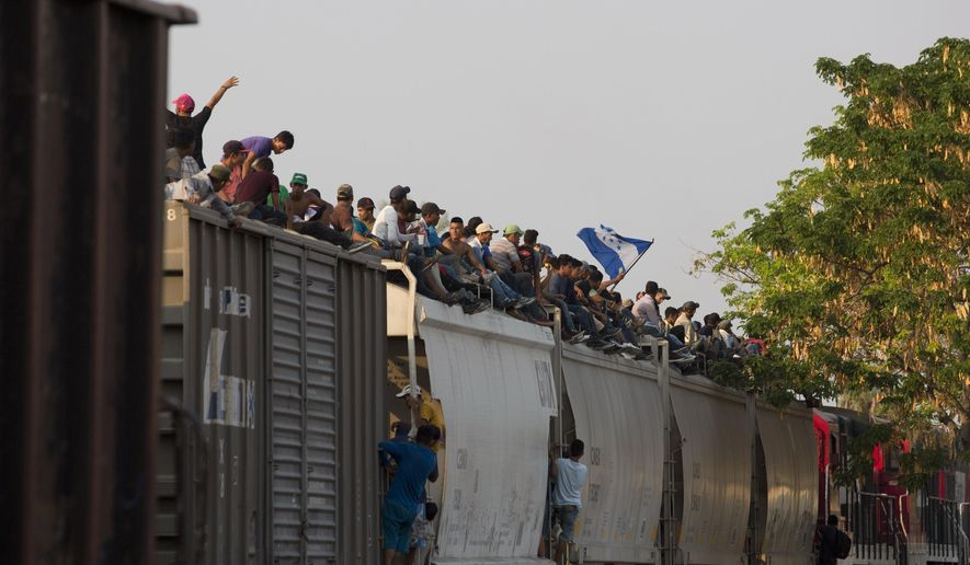 In this April 23, 2019, file photo, Central American migrants ride atop a freight train during their journey toward the U.S.-Mexico border, in Ixtepec, Oaxaca State, Mexico. (AP Photo/Moises Castillo, File)