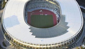 This Sept. 25, 2019, photo shows the new National Stadium, main stadium for the 2020 Tokyo Olympics and Paralympics, in Tokyo.  An international labor union investigating worker safety and the use of migrant workers at facilities for next year's Tokyo Olympics is asking for a joint inspection of build sites and an open interview with workers. (Kyodo News via AP)