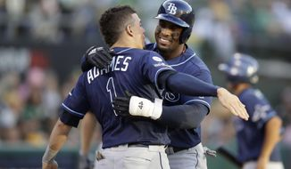 Tampa Bay Rays' Yandy Diaz, right, is congratulated by Willy Adames after hitting a solo home run against the Oakland Athletics during the third inning of an American League wild-card baseball game in Oakland, Calif., Wednesday, Oct. 2, 2019. (AP Photo/Ben Margot)