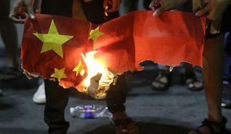 FILE - In this Nov. 20, 2019, file photo, students burn a Chinese flag as they protest against the visit of Chinese President Xi Jinping outside the Presidential palace in Manila, Philippines. The Philippine foreign secretary has ordered via Twitter the filing of a diplomatic protest against China after Chinese coast guard ships reportedly strayed near a Philippine-occupied shoal in the disputed South China Sea. (AP Photo/Aaron Favila, File)