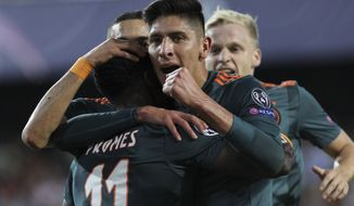 Ajax's Quincy Promes is congratulated by teammates after scoring during the Champions League group H soccer match between Valencia and Ajax, at the Mestalla stadium in Valencia, Wednesday, Oct.2, 2019. (AP Photo/Alberto Saiz)