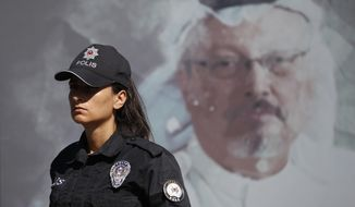 A Turkish police officer walks past a picture of slain Saudi journalist Jamal Khashoggi prior to a ceremony, near the Saudi Arabia consulate in Istanbul, marking the one-year anniversary of his death, Wednesday, Oct. 2, 2019. A vigil was held outside the consulate building Wednesday, starting at 1:14 p.m. (1014 GMT) marking the time Khashoggi walked into the building. (AP Photo/Lefteris Pitarakis)
