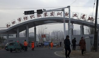 """FILE - In this Dec. 5, 2018, file photo, residents pass by the entrance to the """"Hotan City apparel employment training base"""" where Hetian Taida Apparel Co. has a factory in Hotan in western China's Xinjiang region. The Trump administration on Tuesday, Oct. 1, 2019, announced it is stopping imports of clothing, gold, diamonds and other items believed to have been produced with forced labor by companies based in Brazil, China and Malaysia as well as some gold mined in eastern Congo and diamonds from a region in Zimbabwe. Hetian Taida Apparel Co., Ltd. in Xinjiang, is one of the companies sanctioned. (AP Photo/Ng Han Guan, File)"""