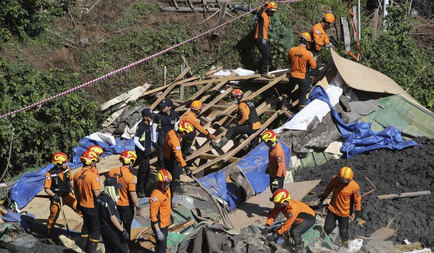 Firefighters search for missing people in an area struck by a landslide after heavy rain in Busan, South Korea, Thursday, Oct. 3, 2019. A powerful typhoon has lashed southern South Korea, leaving nine people dead and five others missing. (Jo Jung-ho/Yonhap via AP)