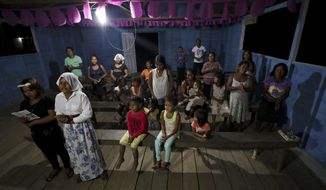 """Worshippers attend a prayer ceremony known as the """"celebration of the word"""" led by Antelmo Pereira at the Catholic church in Santa Rosa, Brazil, Saturday, Sept. 21, 2019. In remote Amazonian communities that are only accessible by boat, villagers can go for months without sacraments that only priests are allowed to deliver - including Mass and confessions, and the faithful have to depend on missionaries such as Pereira that are only allowed to lead prayer ceremonies. (AP Photo/Fernando Vergara)"""