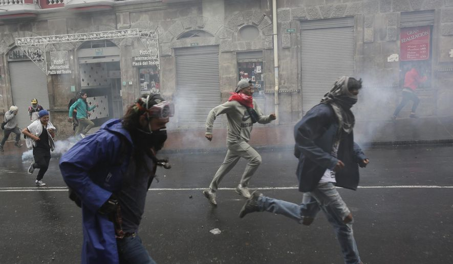 Demonstrators run away after being dispersed by the police during a protest against elimination of fuel subsidies announced by President Lenin Moreno, in Quito, Ecuador, Thursday, Oct. 3, 2019. Moreno announced the end to fuel subsidies and said Tuesday night that he will send congress a proposal to overhaul taxes and labor rules as a way to revitalize the economy. (AP Photo/Dolores Ochoa)