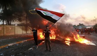 An anti-government protester waves a national flag during a demonstration in Baghdad, Iraq, Thursday, Oct. 3, 2019. Iraqi security forces fired live bullets into the air and used tear gas against a few hundred protesters in central Baghdad on Thursday, hours after a curfew was announced in the Iraqi capital on the heels of two days of deadly violence that gripped the country amid anti-government protests that killed several people in two days. (AP Photo/Hadi Mizban)