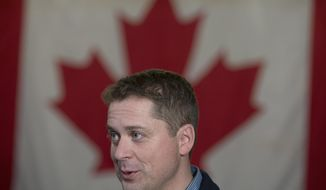 Conservative Leader Andrew Scheer speaks to the media following a campaign rally in Dartmouth, Nova Scotia, on Thursday, Oct. 3, 2019. A Canadian flag is in the background. (Jonathan Hayward/The Canadian Press via AP)