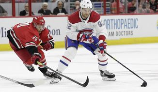 Carolina Hurricanes center Sebastian Aho (20), of Finland, reaches for the puck while Montreal Canadiens left wing Jonathan Drouin (92) skates during the first period of an NHL hockey game in Raleigh, N.C., Thursday, Oct. 3, 2019. (AP Photo/Gerry Broome)