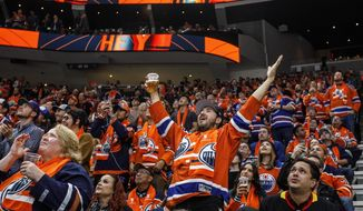 Edmonton Oilers fans celebrate a goal against the Vancouver Canucks during the first period of an NHL hockey game, Wednesday, Oct. 2, 2019 in Edmonton, Alberta. (Jason Franson/The Canadian Press via AP)