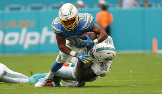 Los Angeles Chargers running back Austin Ekeler (30) is tackled by Miami Dolphins defensive end Taco Charlton (96), during the second half at an NFL football game, Sunday, Sept. 29, 2019, in Miami Gardens, Fla. (AP Photo/Wilfredo Lee)