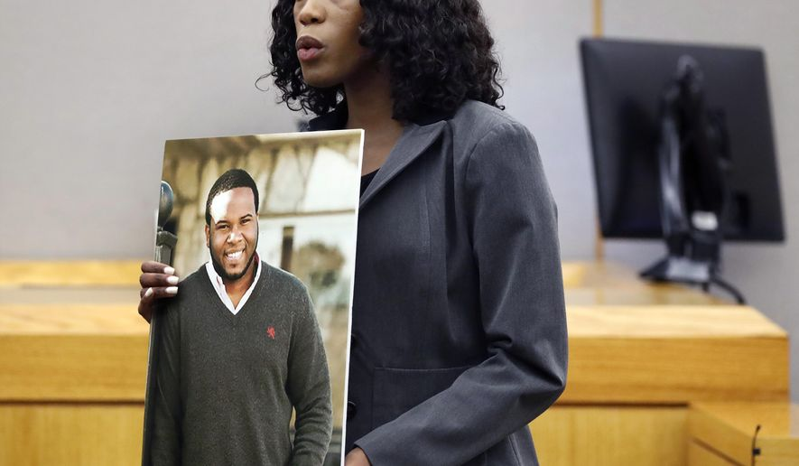 Assistant District Attorney Mischeka Nicholson shows the jury a photo of victim Botham Jean during closing remarks in the sentencing phase of former Dallas Police Officer Amber Guyger's murder trial, Wednesday, Oct. 2, 2019, in Dallas. Guyger, who said she mistook neighbor Botham Jean's apartment for her own and fatally shot him in his living room, was sentenced to a decade in prison. (Tom Fox/The Dallas Morning News via AP, Pool)