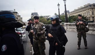 Armed police officers and soldiers patrol after an incident at the police headquarters after in Paris, Thursday, Oct. 3, 2019. A French police union official says an attacker armed with a knife has killed one officer inside Paris police headquarters before he was shot and killed. (AP Photo/Kamil Zihnioglu)